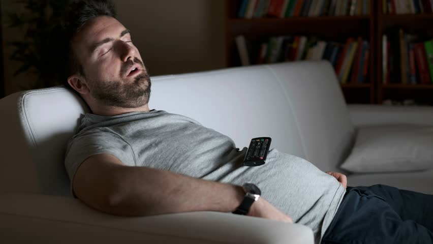 Video is about one lazy man asleep watching television at night alone