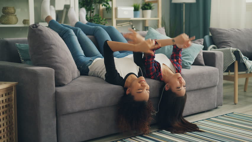 Joyful young ladies are having fun together at home listening to music with smartphone and earphones and dancing moving legs and hands. Friendship and joy concept.