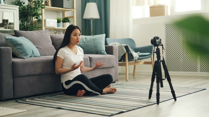 Joyful Asian woman popular blogger is recording video using professional camera talking then showing thumbs-up and waving hand to her followers. Vlogging and technology concept. #1025368856