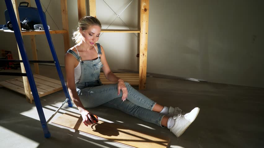 Young girl worker at construction site on a floor measuring tape measure | Shutterstock HD Video #1025391317