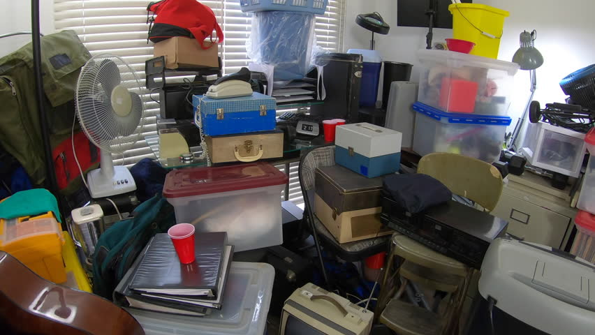 Dolly out through hoarder home room packed full of household items, vintage electronics, business equipment and miscellaneous junk. | Shutterstock HD Video #1025393450