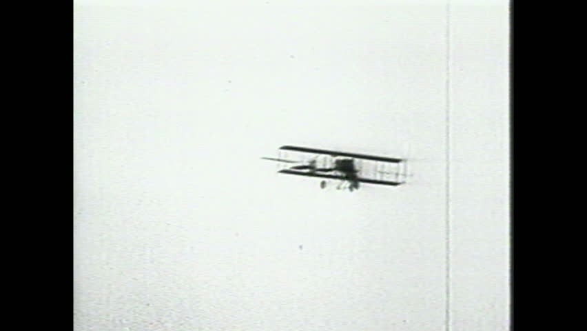 1990s: Men wind propeller on experimental aircraft. Wright Brothers plane rolls across ground. Wright Brother's plane flies through sky. Squadron of military bombers soars through sky.