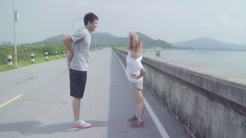 Asian runner couple legs warming and stretching her arms to ready for running on street, Healthy young sweet couple exercise near lake. Lifestyle fit and active couple exercise on street concept. #1025417888