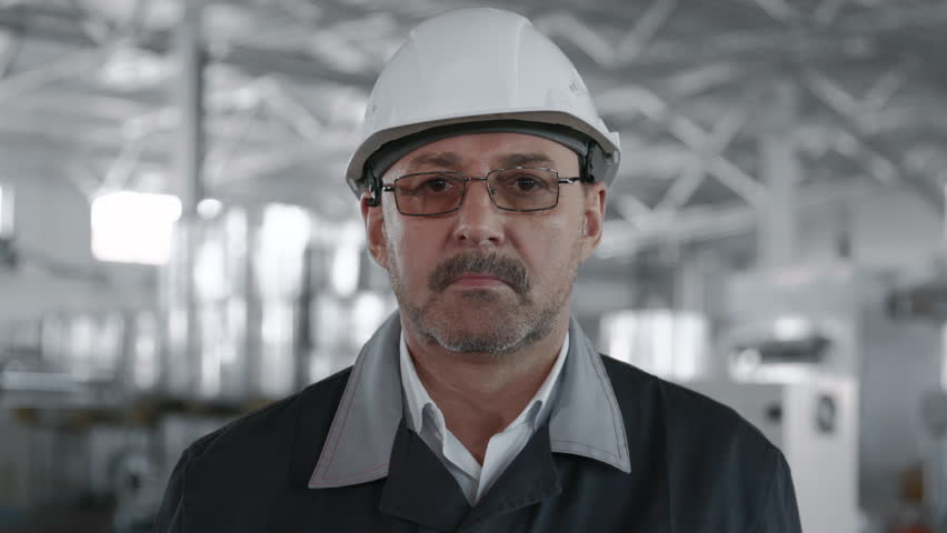 Engineer Planning Manufacture Work. Male Labor Person in Hardhat or Protective Clothes Closeup. Attractive Face of Older Caucasian Technical Foreman. Confident Workman Technician of Machine Tool Line #1025420348