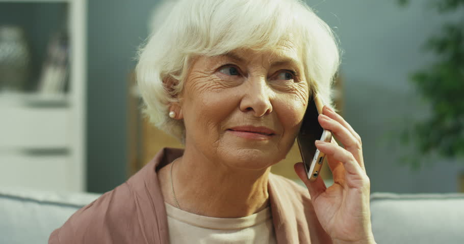 Close up of the old Caucasian woman talking on the mobile phone and smiling in the living room.