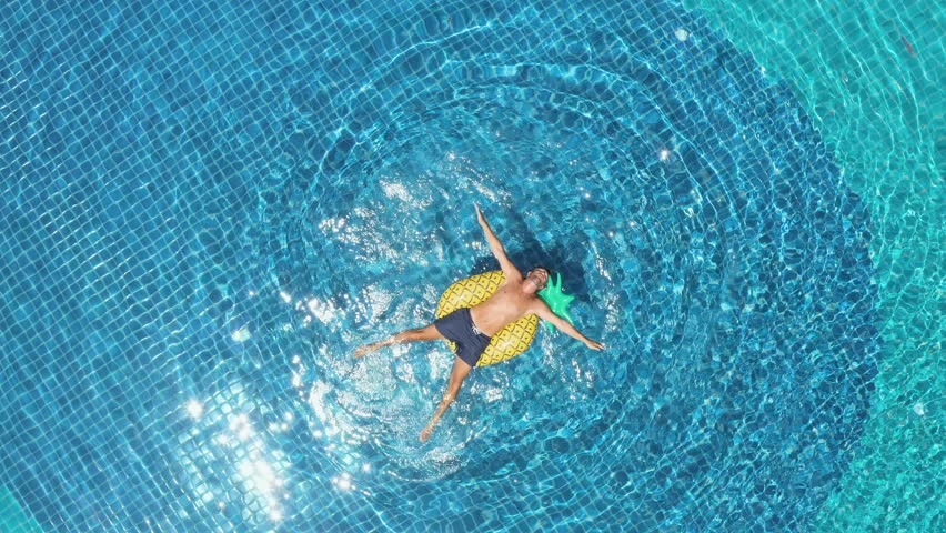 Drone aerial view of Young man floating on inflatable pineapple over blue swimming pool enjoying sunbathing and vacations in tropical destination. People travel tourism holidays concept  | Shutterstock HD Video #1025438267