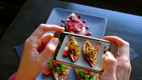 Top view - Woman's hands using a smartphone take pictures of delicious food. 4k. Fresh beautiful waffles with spinach, cherry tomatoes and dessert with spicy pear.