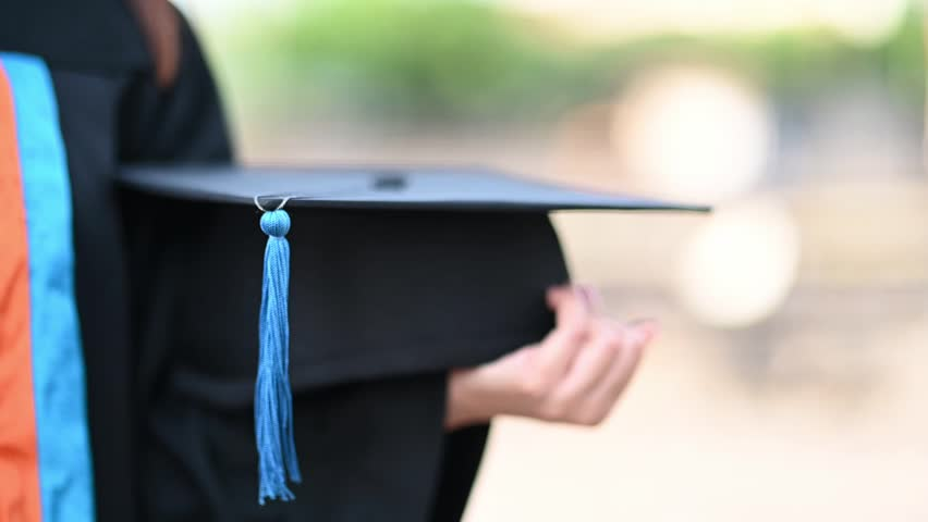 University graduates hold a black hat, blue tassels at the graduation ceremony #1025474114