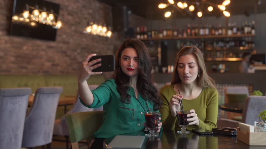 Two beautiful women friends sitting in a cafe, taking photos of themselves while drinking glasses of wine/mulled wine, being very expressive and emotional. Woman in green holding phone | Shutterstock HD Video #1025479274