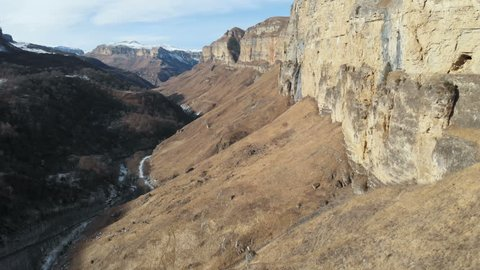 Aerial view of the movement along the rock wall of the canyon in the gorge in the Caucasus. Very close to the rock in winter when there is little snow. 4k