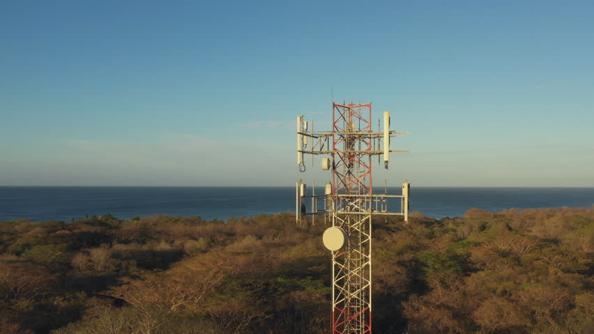 Circling drone shot of radio celltower antenna. Morning light in Guanacaste Province, Costa Rica, Central America. | Shutterstock HD Video #1025507948