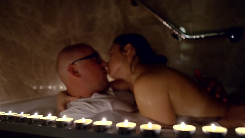 Passionate couple drinks kissing in the Jacuzzi at night by candlelight #1025514143