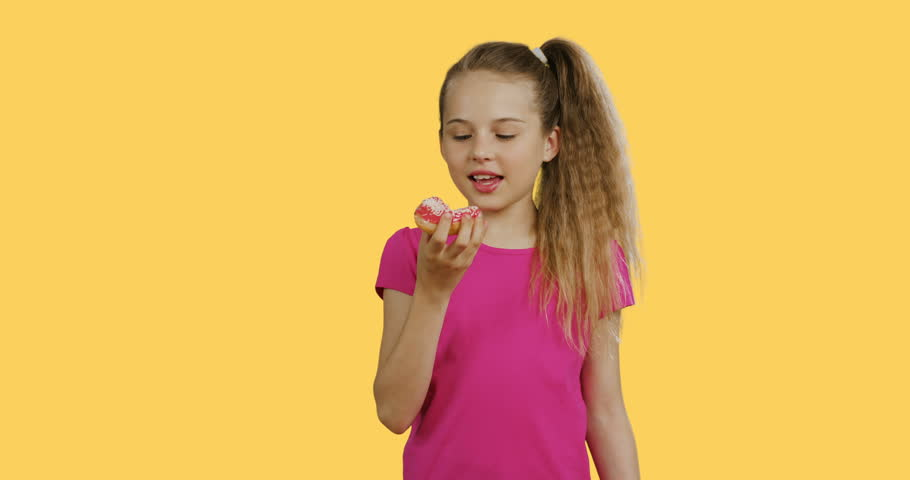 Pretty blonde teenager girl in the pink T-shirt eating a donut and it is very delicious. Yellow wall background. | Shutterstock HD Video #1025517134