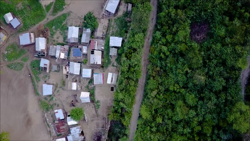 Drone shot over the trees revealing a small village in Haiti.