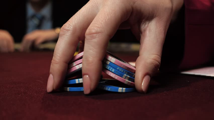 Casino: dealer shuffles the poker chips and performing trick with chips use one hand. Hand close-up.