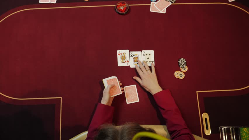 Casino dealer putting cards on red table, poker game, gambling, close-up hands. Top view.