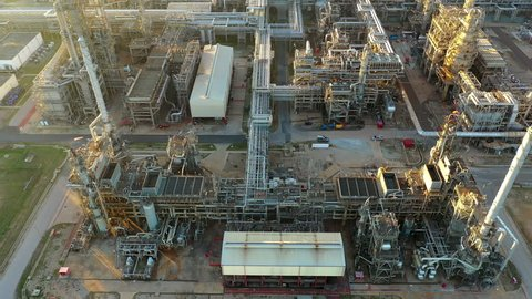 Aerial view of oil refinery and power plant with pipelines and storage tanks.