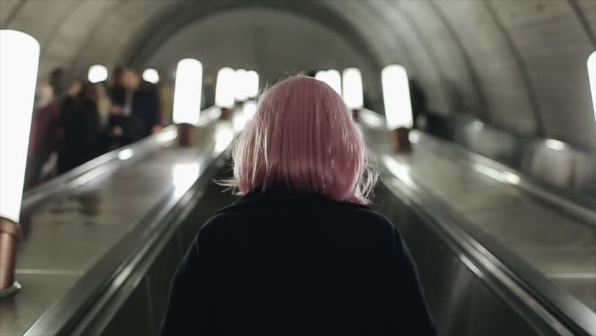 Back view of woman with pink hair using escalator in metro.
