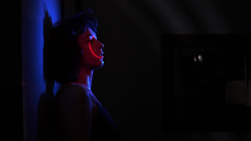 Scared abused woman crying alone in the dark.Victim,violence   Shutterstock HD Video #1025554871