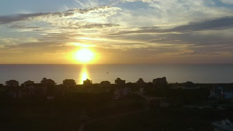 Sunset, flying above ocean and city to the side in Rodanthe, NC, USA.
