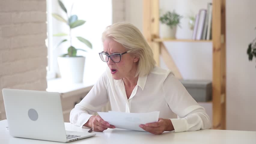 Stressed shocked angry old businesswoman annoyed about computer problem crumpling throwing paper on stuck laptop leaving office workplace quit job feel unable to work frustrated hate negative emotion | Shutterstock HD Video #1025576933