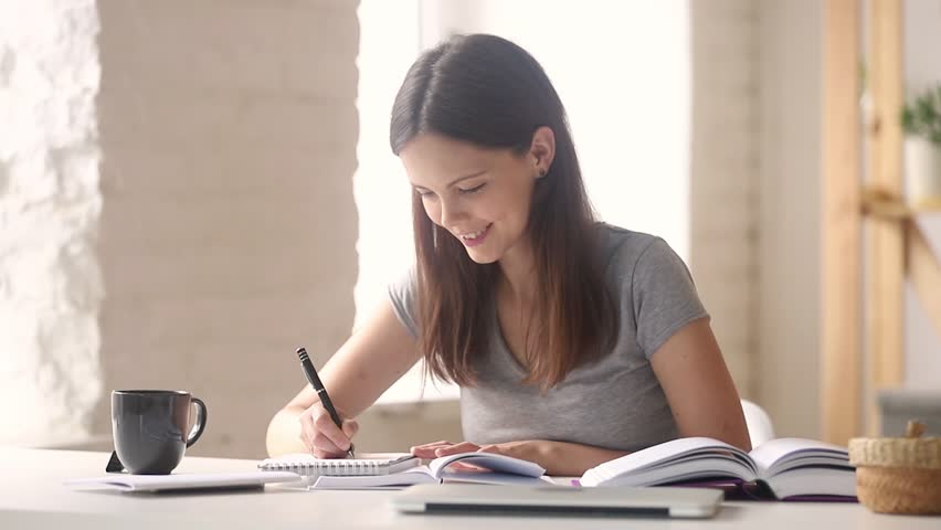 Teen girl high school college university student learning making notes writing essay in notebook doing academic research preparing for exam coursework work with books sitting at desk studying at home Royalty-Free Stock Footage #1025576936