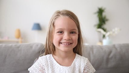 Funny little girl smiling looking at camera at home, cute kid talking to webcam making online video call or recording vlog having fun, preschool child with pretty face waving hand sitting on sofa