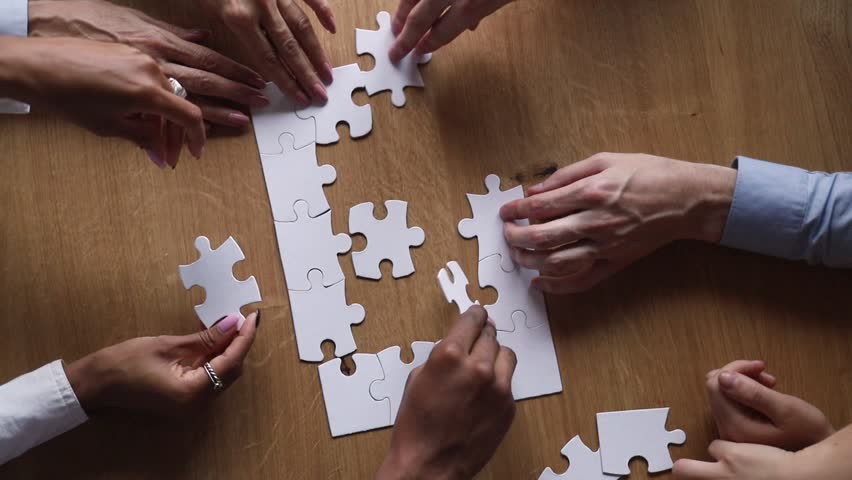 Hands of diverse business team people collaborate assemble puzzle together connect pieces at desk find common purpose solution engaged in help support contribute in teamwork concept top close up view  Royalty-Free Stock Footage #1025577008