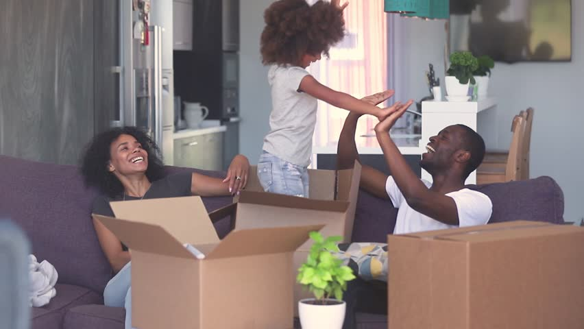 Happy child girl jump out of box give high five to dad play with black parents in living room, african family and kid daughter laughing having fun pack unpack enjoy relocation moving in new home Royalty-Free Stock Footage #1025577017
