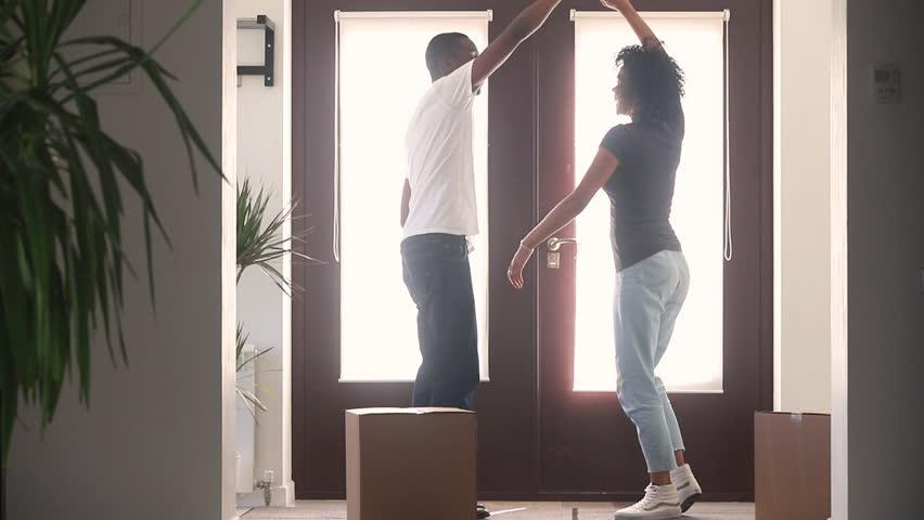 Happy african american couple first time home buyers dancing in hallway moving with boxes celebrate relocation buy new house, excited black family tenants renters having fun enjoy renovation mortgage Royalty-Free Stock Footage #1025577026
