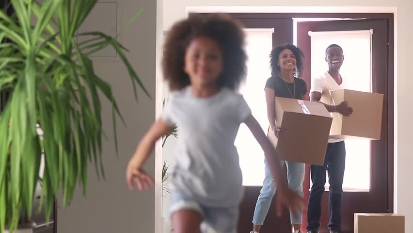 Happy black family moving in new home, excited african american parents and cute child daughter tenants owners holding boxes enter big house kid running in hallway, mortgage, relocation and welcome