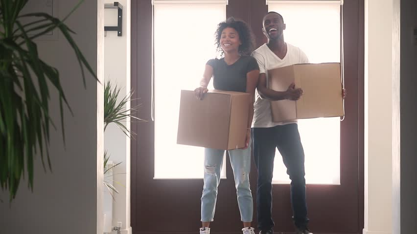 Happy black couple first time home buyers holding boxes talking embracing standing in hallway coming into big modern house, african american renters tenants relocating on moving day, family mortgage Royalty-Free Stock Footage #1025577041