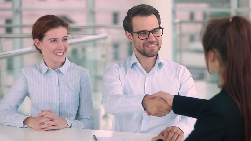 Happy young couple first time home buyers renters sign mortgage loan investment contract sale purchase agreement make real estate deal meeting realtor, customers get new house keys handshake agent Royalty-Free Stock Footage #1025577044