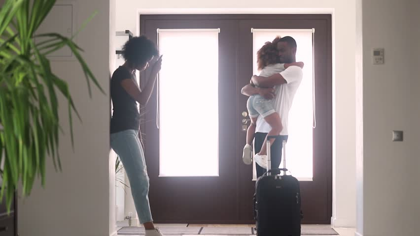 African dad talking to sad child daughter in hallway leaving family home with goodbye hug, black father embracing consoling kid say bye to upset little girl, parents divorce, shared custody concept