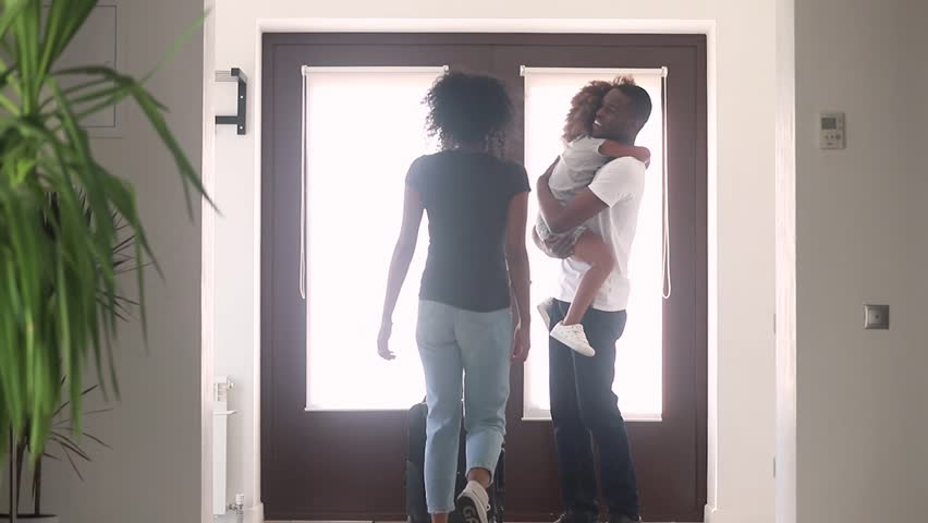 Happy african kid daughter and wife excited to meet american dad coming returning arriving home with suitcase, excited child girl running hugging daddy at door, black family welcome reunion concept
