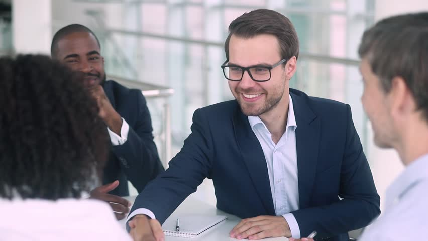 Satisfied caucasian boss hr negotiator talking shake hand of african american candidate partner client making deal, hiring or thanking for collaboration at diverse group business meeting negotiations