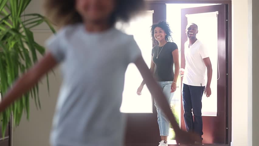 Funny happy cute african american child girl running into new big house exploring moving in, black family real estate mortgage owners tenants entering own home with excited kid having fun in hallway