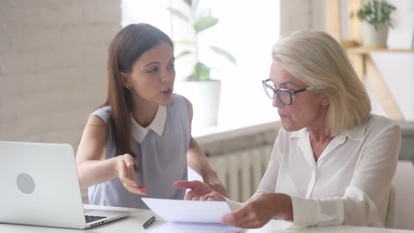 Angry dissatisfied old woman arguing meeting young manager dealing with client complaints on bad bank contract service claiming compensation, mad customer demanding legal fight insurance dispute