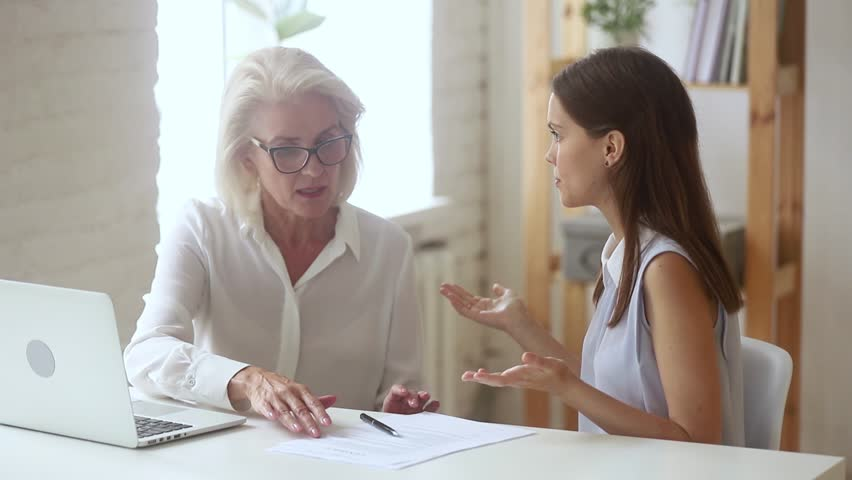 Angry young woman argue with old manager claim rights protection having legal fight conflict, dissatisfied customer demanding compensation for bad contract service meeting lawyer, client complaints