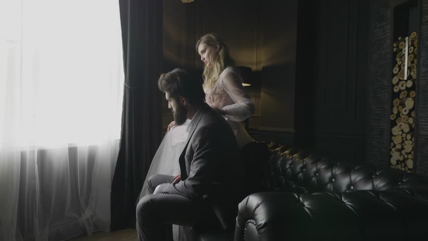 Slow motion severe bearded man in grey sits on black leather sofa and blond lady touches shoulder at bright window | Shutterstock HD Video #1025589038