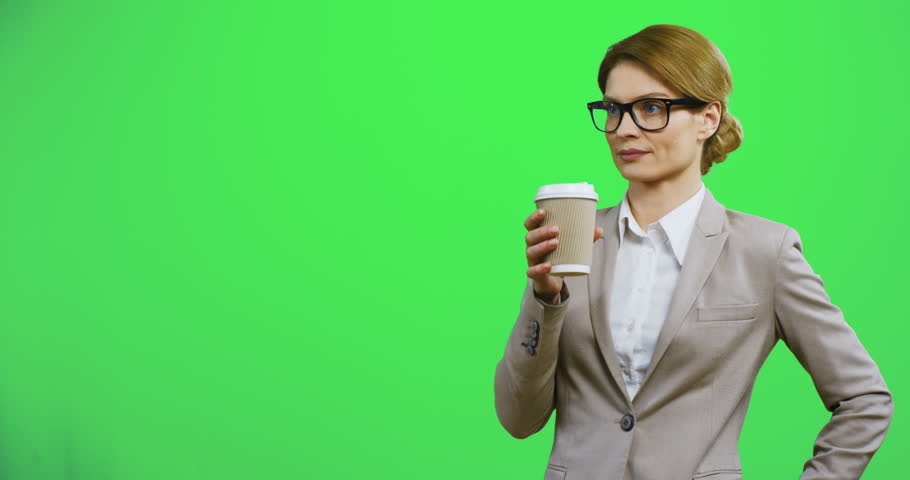 Caucasian good looking and stylish businesswoman in glasses standing on the chroma key background and drinking coffee, while waiting for somebody. Alpha channel.