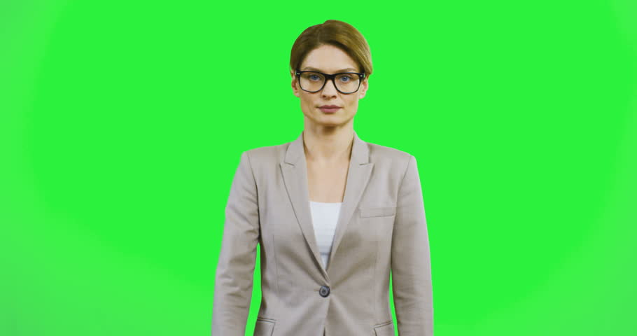 Caucasian attractive young businesswoman in glasses posing and smiling to the camera while crossing her hands in front of her on the green screen. Portrait shot.