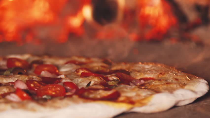 Pizza in the oven. Camera moves righ on the slider.The fire burns in the oven. Pizza oven. Slow motion burning bonfire. Pizza oven. Bonfire is on fire. Slow motion burning fire.
