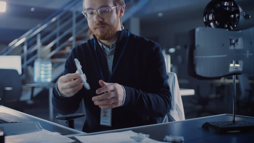 Electronics Development Engineer Working at His Desk, Fits Component into Prototype. Professionals Work in the Advanced Technology Designing Agency. Modern Research Centre Using 3D Printing