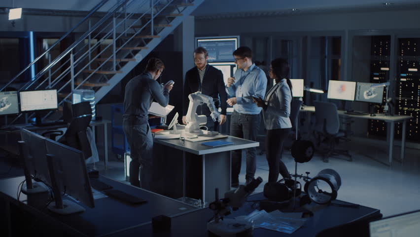 Team of Electronics Development Engineers Standing at the Desk Working on Robot Arm Prototype. Specialists Working on Ultra Modern Industrial Design, Using Machine Learning. Slow Motion | Shutterstock HD Video #1025609603