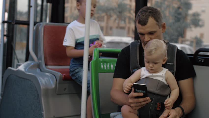 Dad riding in the bus with elder son and one year old baby daughter. Everyone watching fathers smart phone | Shutterstock HD Video #1025612816
