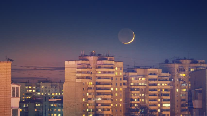 Beautiful waxing crescent moon setting behind city skyline buildings rooftops at night. Zoom in. Timelapse, 4K UHD. | Shutterstock HD Video #1025614211