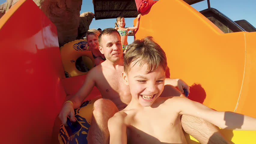 Happy family - healthy father going down a bright water slide with his kid - little son. Parents with children laughing going down waterslide at waterpark on beautiful summer day on sunny vacations.