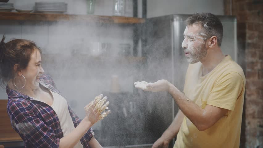 Happy couple playing with flour in kitchen, blowing it into each other faces and laughing.