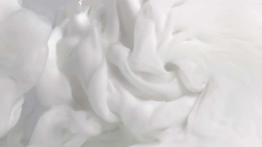 Macro 4k slow motion of milk cream waves and drops splash mixing with each other in water. #1025645246